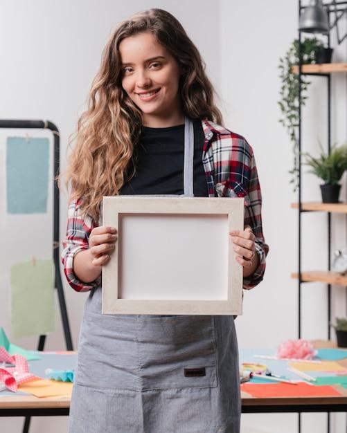 Femme souriante tenant un cadre d'image vide blanc en regardant la caméra Photo gratuit