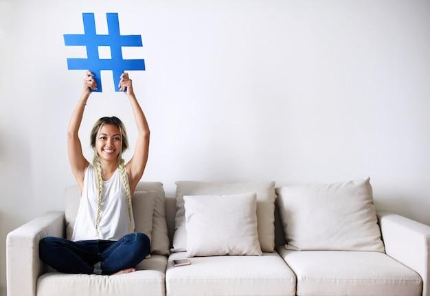 Femme souriante tenant un concept de média social pour le signe hashtag Photo Premium