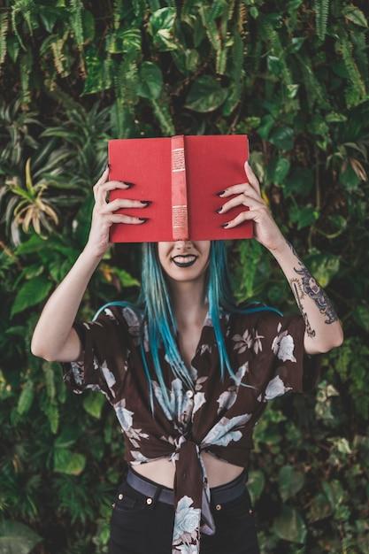 Femme souriante tenant un livre rouge devant ses yeux Photo gratuit