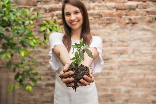 Femme souriante tenant une petite plante avec de la terre Photo gratuit