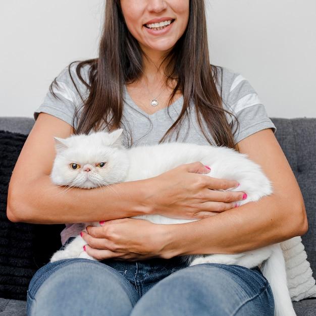Femme souriante tenant son chat Photo gratuit