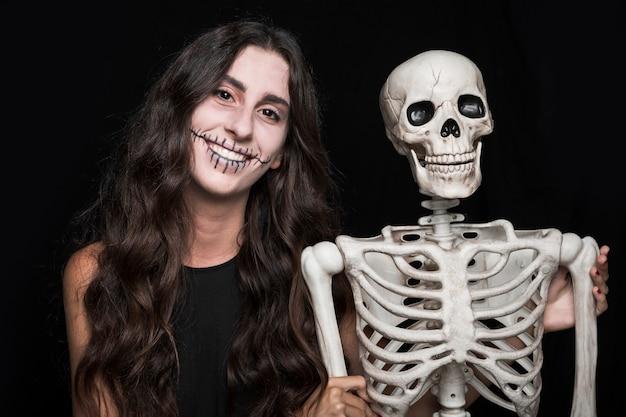 Femme souriante tenant squelette Photo gratuit