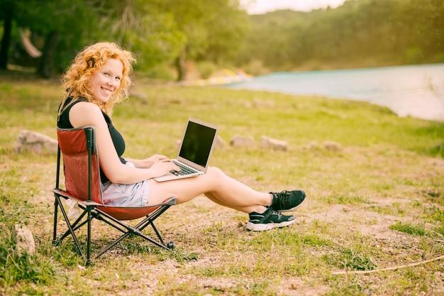 Femme souriante travaillant sur un ordinateur portable à l'extérieur Photo gratuit