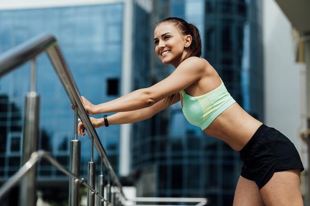 Femme souriante utilisant une balustrade pour s'étirer Photo gratuit