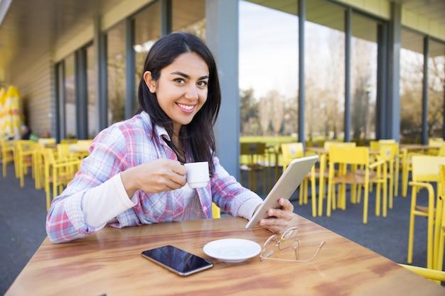 Femme souriante utilisant des gadgets et buvant du café au café Photo gratuit