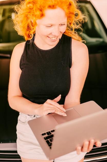 Femme souriante, utilisation, ordinateur portable, penchement femme Photo gratuit