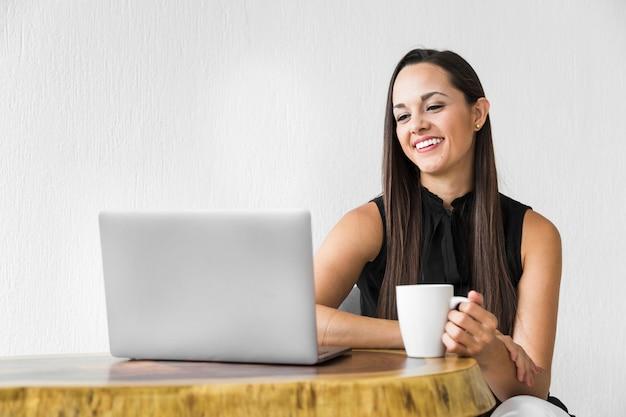 Femme souriante et vérifiant son ordinateur portable Photo gratuit