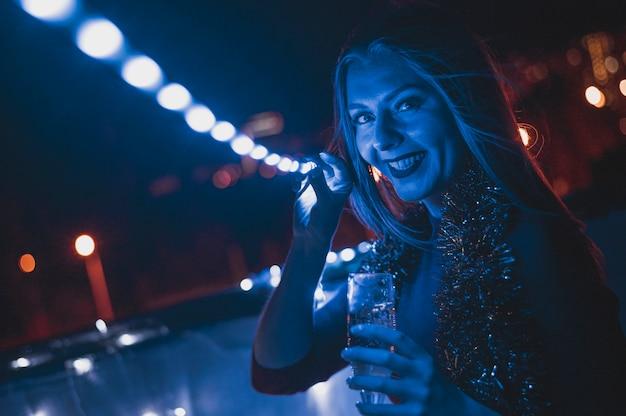 Femme souriante avec un verre de champagne et des lampes bleues Photo gratuit