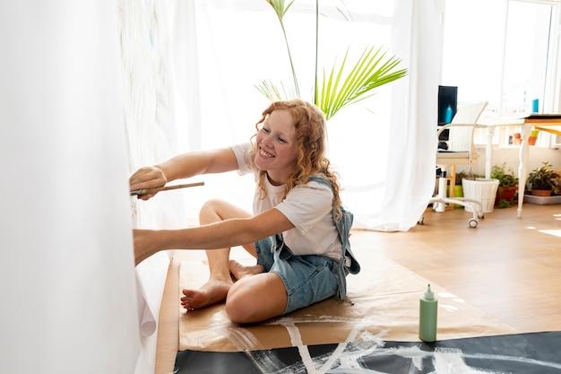 Femme souriante vue de côté, peinture sur le mur Photo gratuit