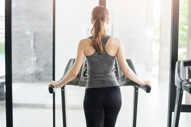 Femme de sport dos jogging sur tapis roulant en salle de sport, mode de vie sain Photo Premium