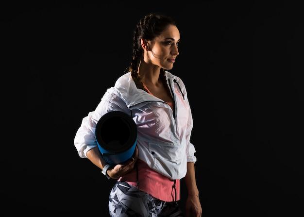 Femme de sport sur fond sombre avec tapis Photo Premium