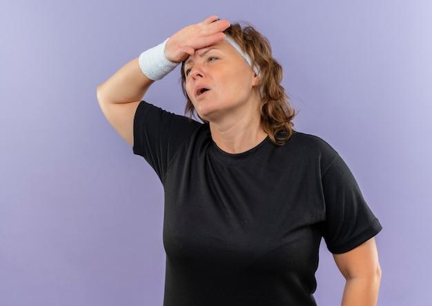Femme Sportive D'âge Moyen En T-shirt Noir Avec Bandeau à Côté Avec La Main Sur La Tête Fatiguée Et épuisée Après L'entraînement Debout Sur Le Mur Bleu Photo gratuit