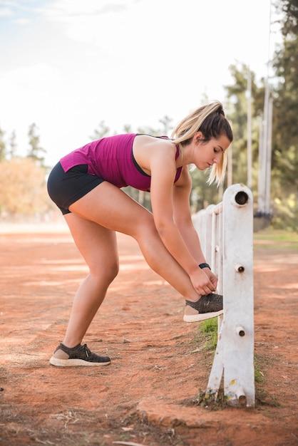 Femme sportive attachant des chaussures sur la piste du stade Photo gratuit