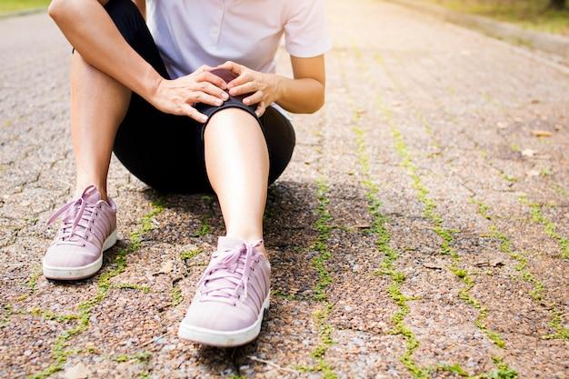 Une femme sportive a des douleurs au genou ou des blessures à la jambe après un travail dans un parc Photo Premium