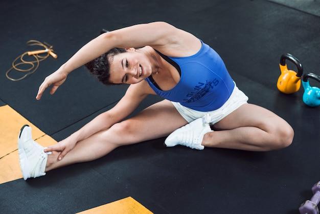 Une femme sportive faisant des exercices d'étirement sur le sol dans une salle de sport Photo gratuit
