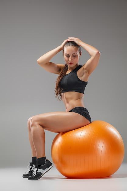 Femme Sportive Faisant Des Exercices Sur Un Fitball Photo gratuit