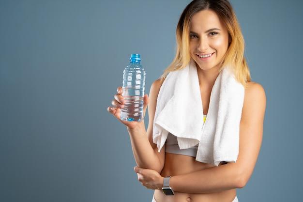 Femme sportive sur fond gris, tenant une bouteille d'eau Photo Premium