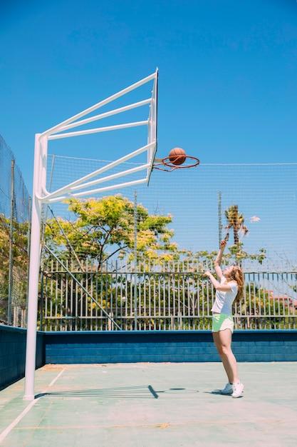 Femme sportive, lancer la balle dans le cerceau sur fond de nature Photo gratuit
