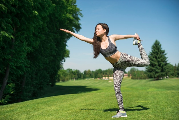 Femme sportive pratiquant le yoga en plein air Photo gratuit