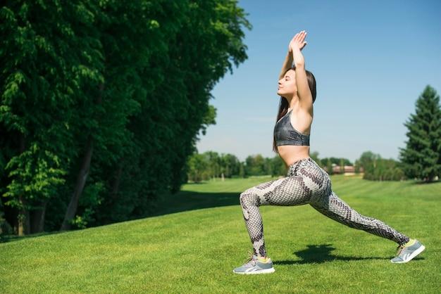Femme sportive pratiquant le yoga en plein air Photo gratuit