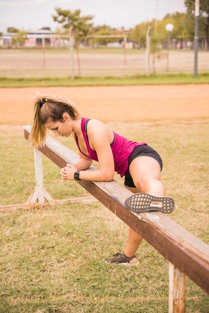Femme sportive qui s'étend sur la piste du stade Photo gratuit