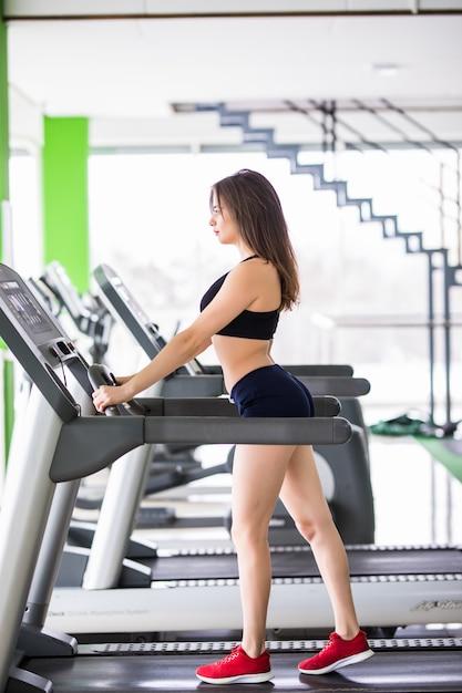 Femme Sportive S'exécute Sur Un Simulateur De Sport Dans Un Centre De Fitness Moderne Habillé En Vêtements De Sport Noir Photo gratuit