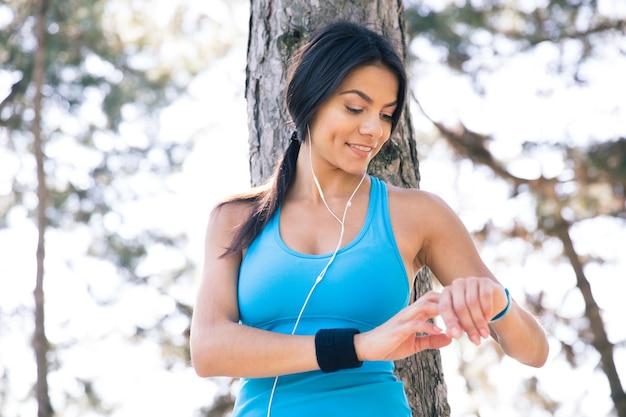 Femme Sportive Souriante à L'aide De Montre Intelligente Photo Premium