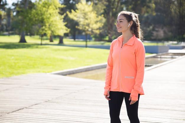 Femme sportive souriante relaxante dans le parc de la ville Photo gratuit