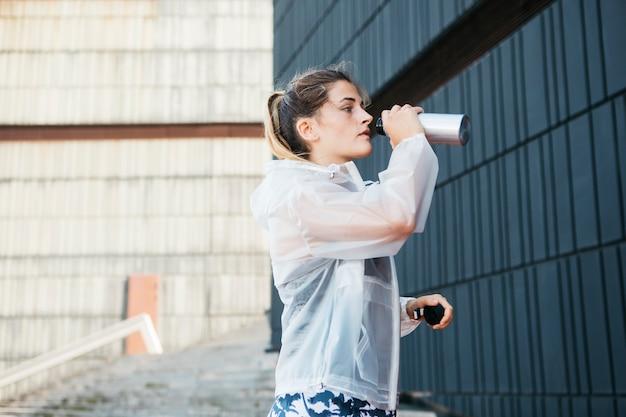 Femme sportive avec veste de pluie en milieu urbain Photo gratuit
