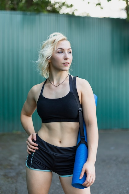 Femme sportive vue de face avec tapis de yoga Photo gratuit