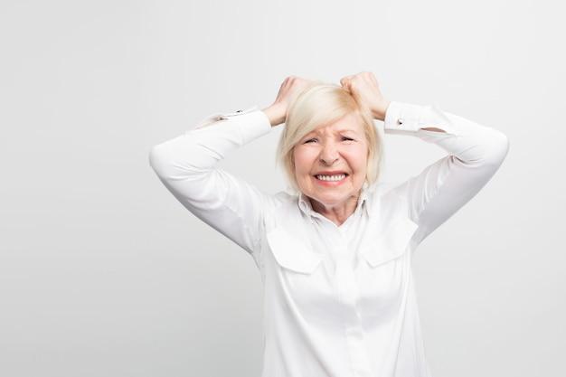 Une Femme Stressante Et Vieille Garde Ses Mains Sur Sa Main Et Montre Des émotions De Dépression. Elle Est Désespérée. Photo Premium