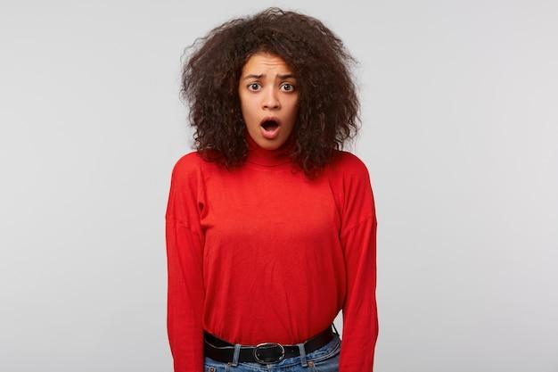 Une Femme Stupéfaite Avec Une Coiffure Afro Regarde Devant Et Garde La Bouche Ouverte, Regarde étonnamment Photo gratuit