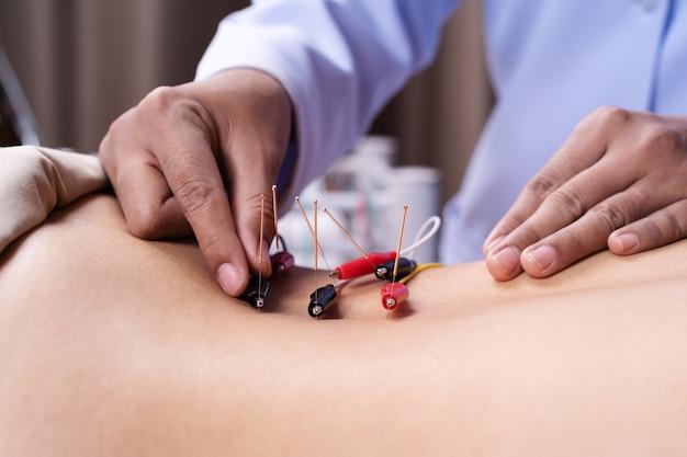 Femme Subissant Un Traitement D'acupuncture Avec Stimulateur électrique Au Dos Photo Premium