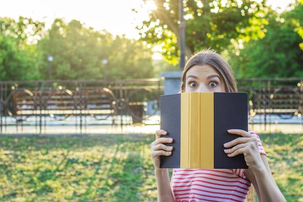 Femme surprise et choquée dans le parc avec un livre. Photo Premium