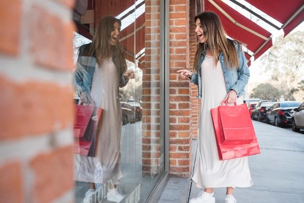 Femme surprise avec des paquets de shopping en regardant les vitrines Photo gratuit