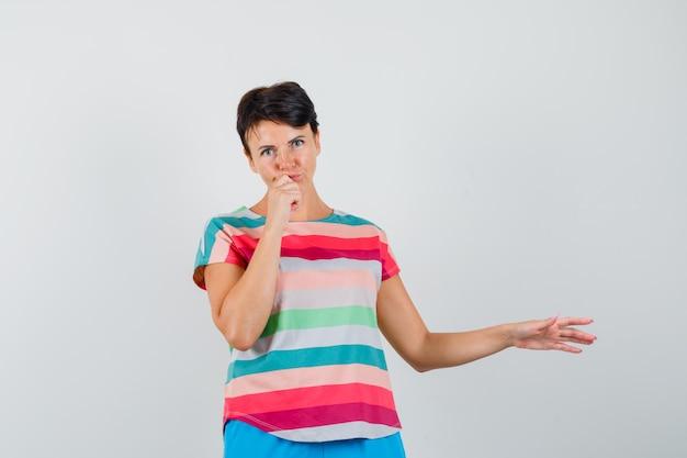 Femme En T-shirt Rayé, Pantalon écartant Le Bras Tout En Pensant Et à L'hésitation Photo gratuit