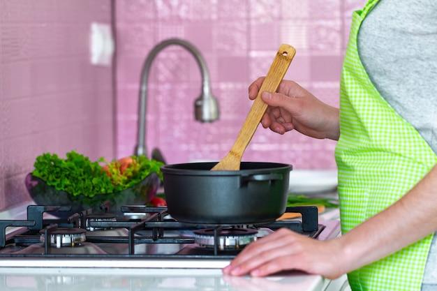 Femme en tablier debout près de la cuisinière et faisant cuire la soupe à la cuisine à la maison. préparation de la cuisine pour la famille pour le dîner. nettoyer des aliments sains et une nutrition adéquate. Photo Premium