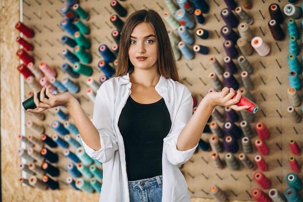 Femme tailleur choisissant des fils dans une usine Photo gratuit