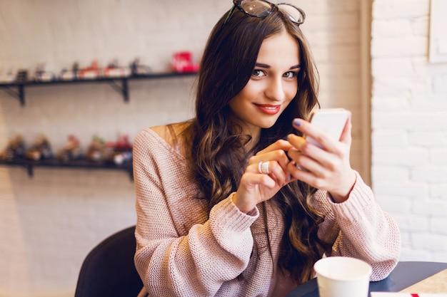 Femme Tapant écrire Un Message Sur Un Téléphone Intelligent Dans Un Café Moderne. Image Recadrée De Jeune Jolie Fille Assise à Une Table Avec Café Ou Cappuccino à L'aide De Téléphone Mobile. Photo gratuit