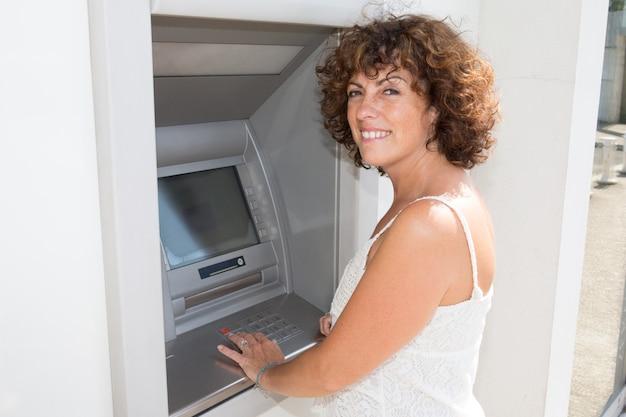 Femme tape son code sur un distributeur de billets de banque Photo Premium