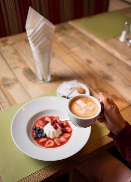 Femme, à, tasse café, et, blanc laiteux, pouding crémeux, à, confiture, et, baies Photo Premium
