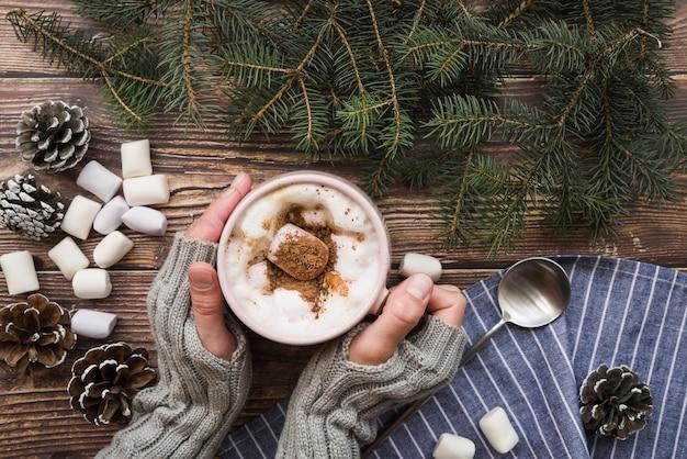 Femme avec une tasse de café et des guimauves Photo gratuit