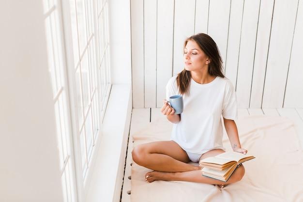 Femme avec une tasse et un livre, profitant de la lumière du soleil Photo gratuit