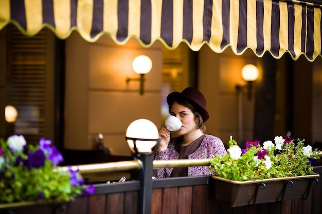 Femme avec une tasse de thé assis dans un café. Photo Premium