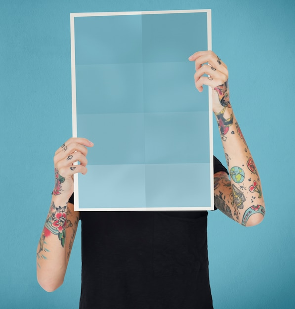 Femme tatouée tenant un papier vierge Photo Premium