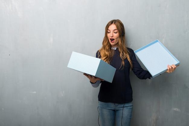 Femme de télémarketing tenant une boîte-cadeau en mains Photo Premium