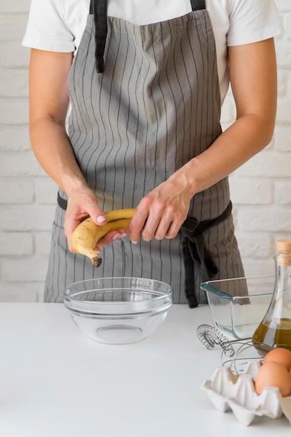 Femme Tenant La Banane Sur Un Bol Photo gratuit