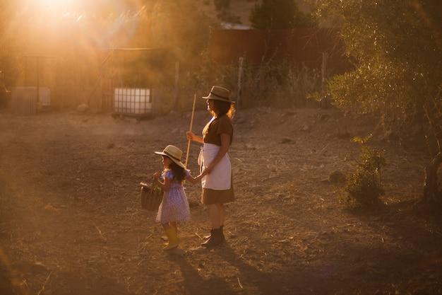 Femme tenant un bâton debout avec sa fille dans le champ Photo gratuit