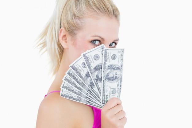 Femme tenant des billets de banque ventilés devant le visage Photo Premium