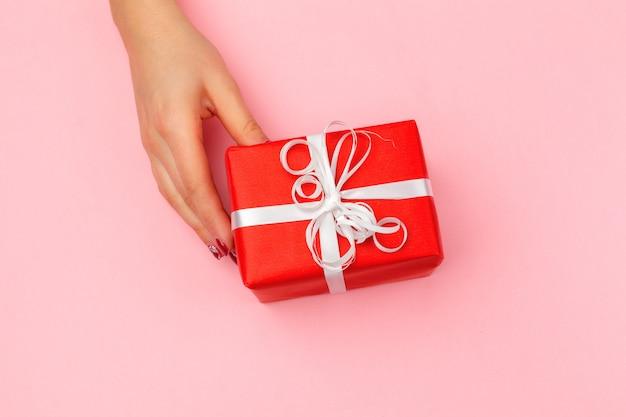 Femme tenant une boîte cadeau sur fond de couleur Photo Premium